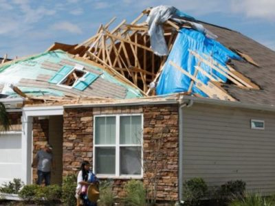 A young woman removes personal belongings from her damaged home Sept. 6, 2019, after a tornado spawned by Hurricane Dorian ripped apart her roof in Carolina Shores, N.C. (CNS photo/Jonathan Drake, Reuters) See story to come.